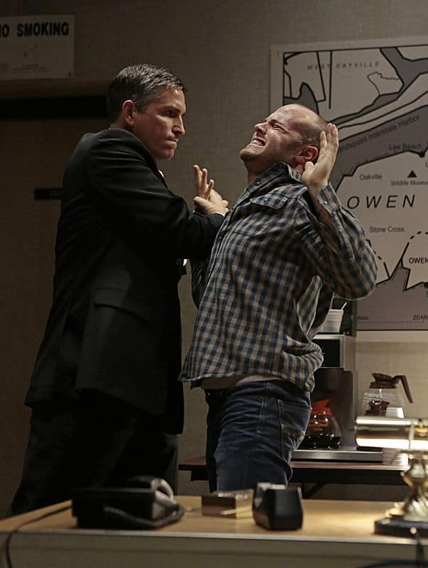While forced to ride out a storm in a coastal town with a group of local residents, Reese (Jim Caviezel, left) comes to blows with one of them (Dennis Flanagan, right)
