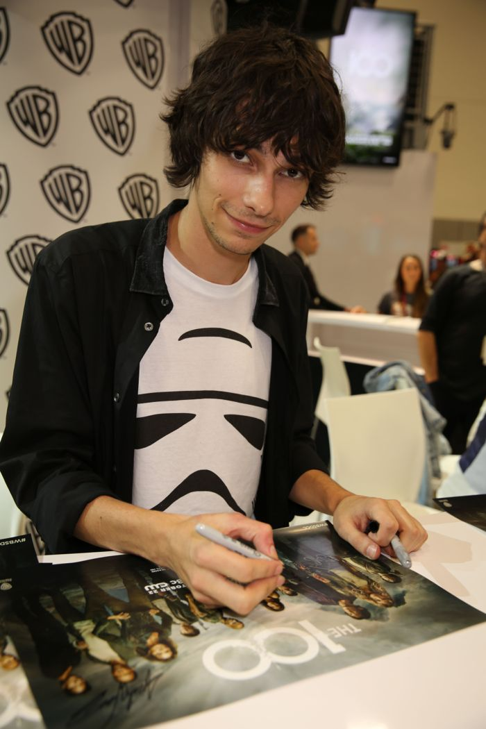 THE 100's Devon Bostick signs a poster of the series at the Warner Bros. booth at Comic-Con 2014.