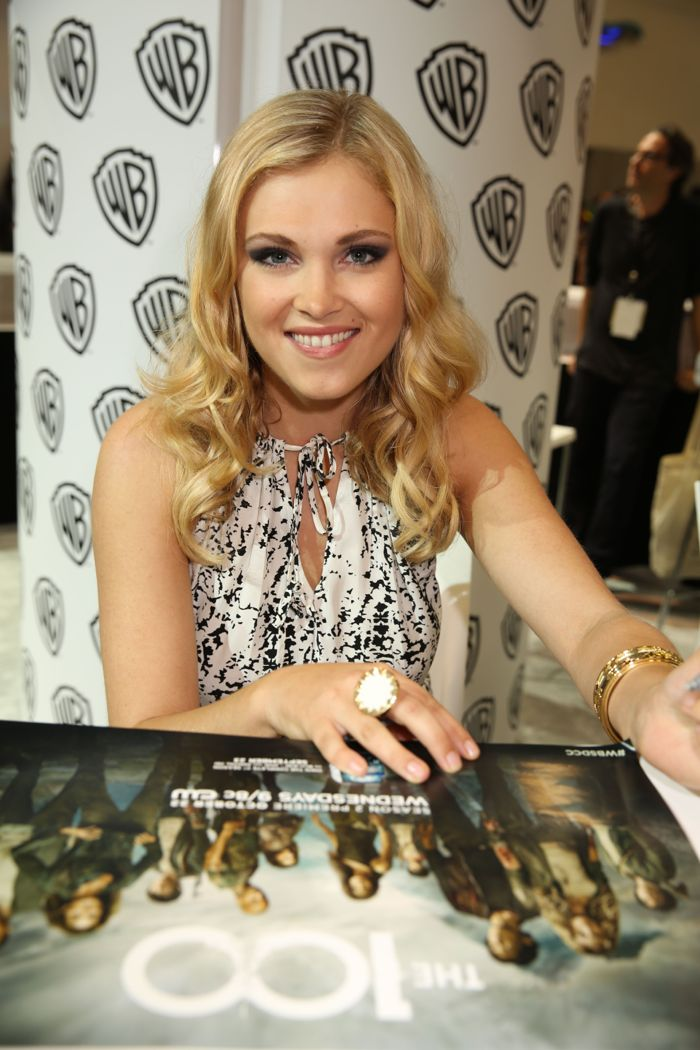 THE 100 star Eliza Taylor smiles and signs for fans at the Warner Bros. booth at Comic-Con 2014. #WBSDCC (©2014 WBEI. All rights reserved.)
