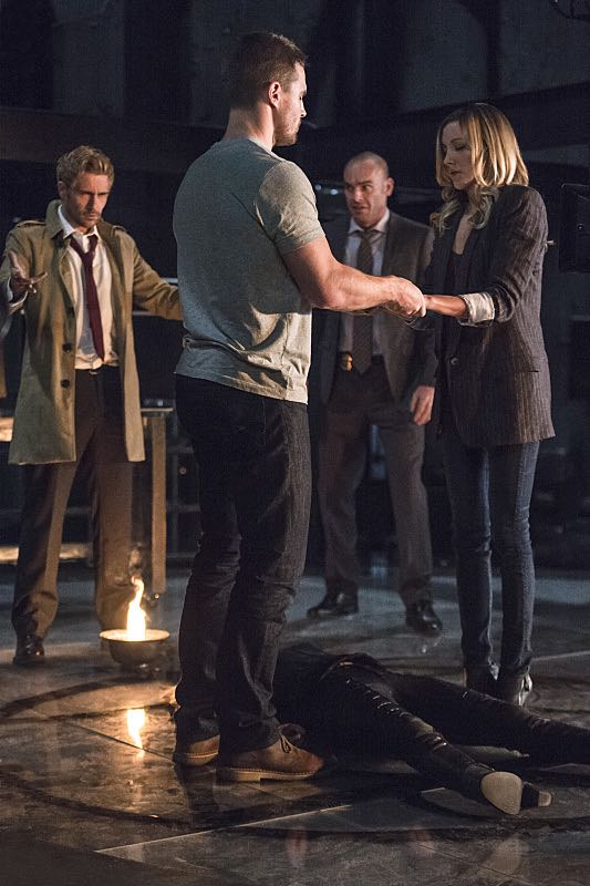"""Arrow -- """"Haunted"""" -- Image AR404B_0060b.jpg -- Pictured (L-R): Matt Ryan as Constantine, Stephen Amell as Oliver Queen, Paul Blackthorne as Detective Quentin Lance and Katie Cassidy as Laurel Lance -- Photo: Cate Cameron/ The CW -- © 2015 The CW Network, LLC. All Rights Reserved."""
