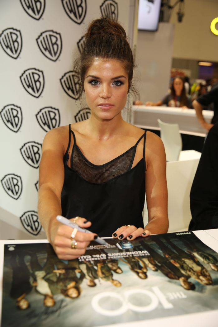 Marie Avergopoulos of THE 100 signs for fans at the Warner Bros. booth at Comic-Con 2014