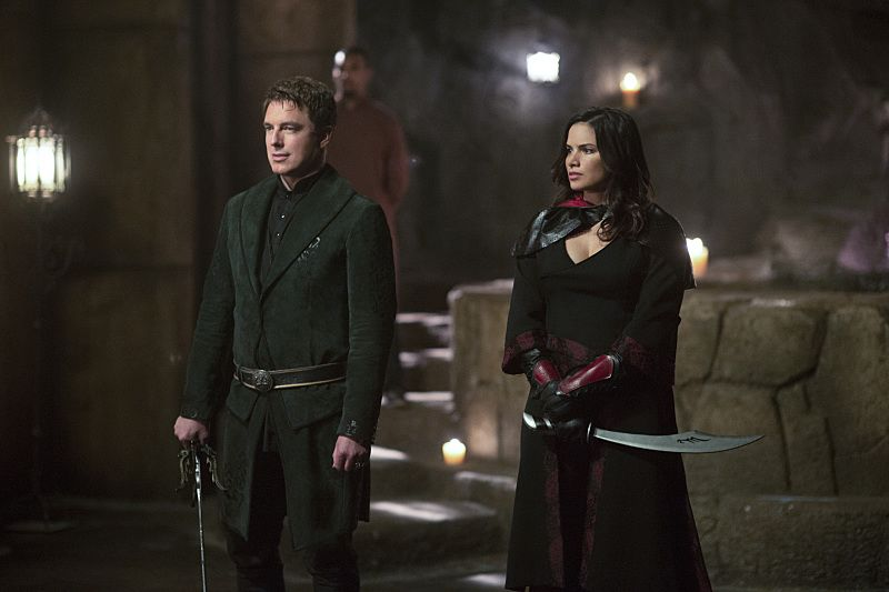 "Arrow -- ""Restoration"" -- Image AR403B_0035b.jpg -- Pictured (L-R): John Barrowman as Malcolm Merlyn and Katrina Law as Nyssa al Ghul -- Photo: Diyah Pera /The CW -- © 2015 The CW Network, LLC. All Rights Reserved."