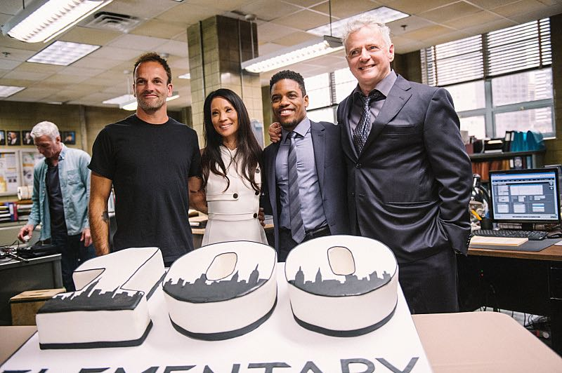 """""""Henny Penny The Sky Is Falling"""" -- The cast of ELEMENTARY celebrates their milestone 100th episode with a cake-cutting ceremony Pictured (L-R) Picture (L-R) Jonny Lee Miller, Lucy Liu, Jon Michael Hill and Aidan Quinn Photo: Michele Crowe /CBS ©2016 CBS Broadcasting Inc. All Rights Reserved."""