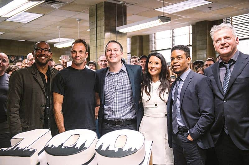 """""""Henny Penny The Sky Is Falling"""" -- The cast of ELEMENTARY celebrates their milestone 100th episode with a cake-cutting ceremony Pictured (L-R) Executive Producer Carl Beverly, Jonny Lee Miller, Executive Producer Rob Doherty, Lucy Liu, Jon Michael Hill and Aidan Quinn Photo: Michele Crowe /CBS ©2016 CBS Broadcasting Inc. All Rights Reserved."""