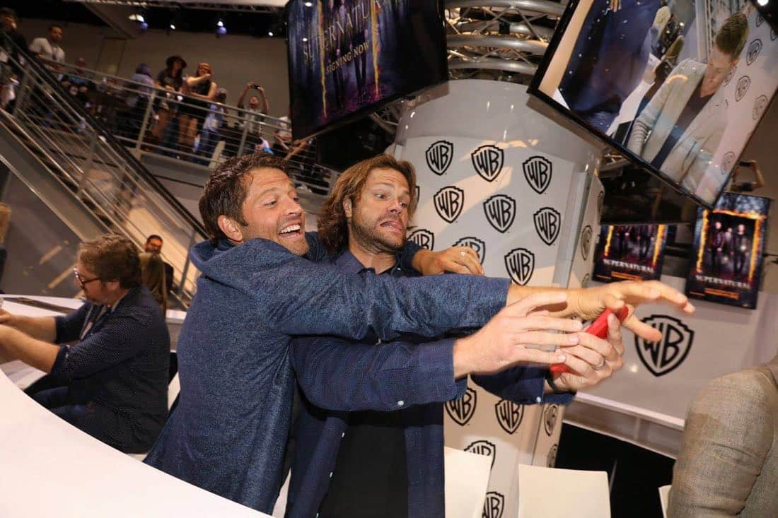 SUPERNATURAL stars Misha Collins (left) and Jared Padalecki have some fun at the Warner Bros. booth at Comic-Con 2017 on Sunday, July 23. #WBSDCC (© 2017 WBEI. All Rights Reserved)