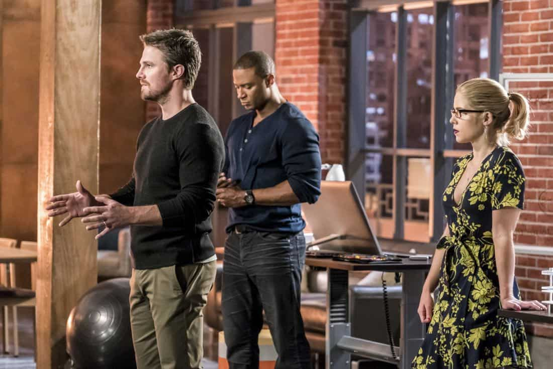 "Arrow -- ""Divided"" -- Image Number: AR610b_0105.jpg -- Pictured (L-R): Stephen Amell as Oliver Queen/Green Arrow, David Ramsey as John Diggle/Spartan and Emily Bett Rickards as Felicity Smoak -- Photo: Daniel Power/The CW -- © 2018 The CW Network, LLC. All Rights Reserved."