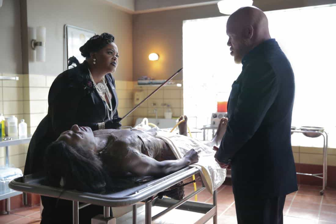 """Black Lightning -- """"Black Jesus"""" -- Image BLK104b_0351rb.jpg -- Pictured (L-R): Jill Scott as Lady Eve and Marvin """"Krondon"""" Jones III as Tobias -- Photo: Carin Baer/The CW -- © 2018 The CW Network, LLC. All rights reserved."""