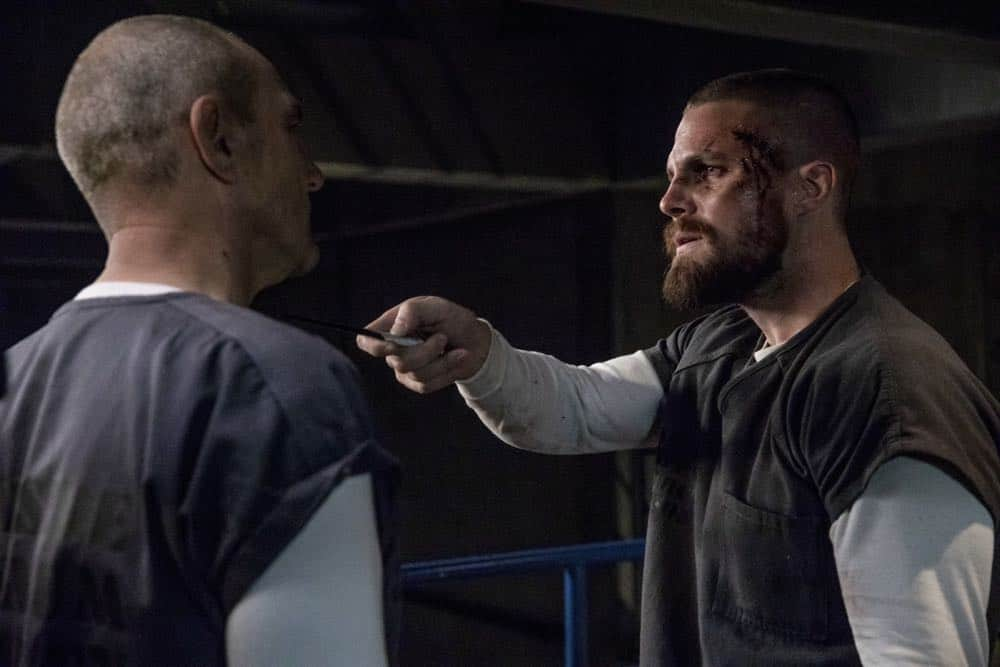 "Arrow -- ""Crossing Lines"" -- Image Number: AR703a_0200b -- Pictured (L-R): Vinnie Jones as Danny ""Brick"" Brickwell and Stephen Amell as Oliver Queen/Green Arrow  -- Photo: Jack Rowand/The CW -- © 2018 The CW Network, LLC. All Rights Reserved."